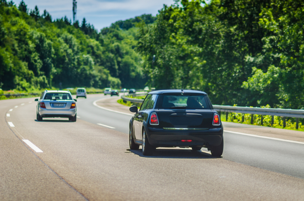 Black small car on the German Autobahn in sunny day