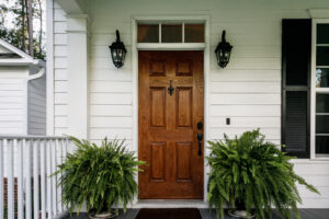 Brown Wood Front Door of a White Siding Southern House
