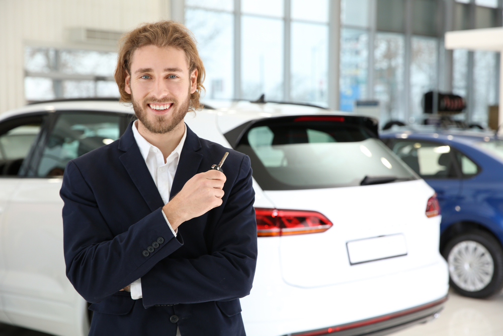 Young car salesman with key in dealership. Space for text