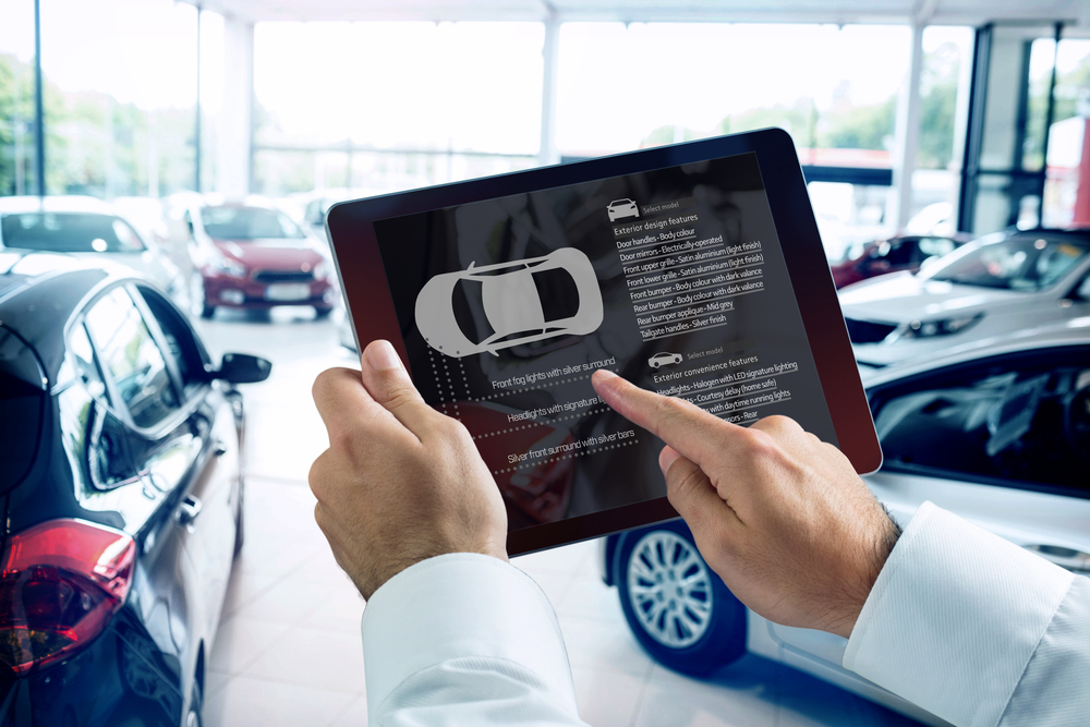 Businessman using digital tablet next to smartphone against view of row new car