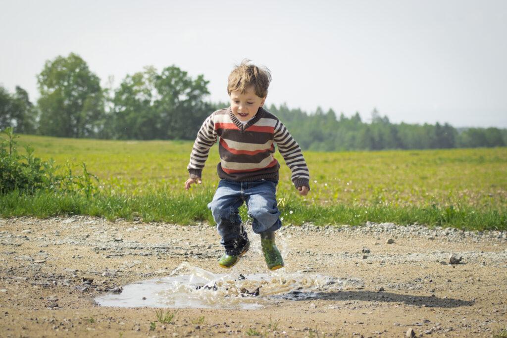 Boy jumping near grass at daytime