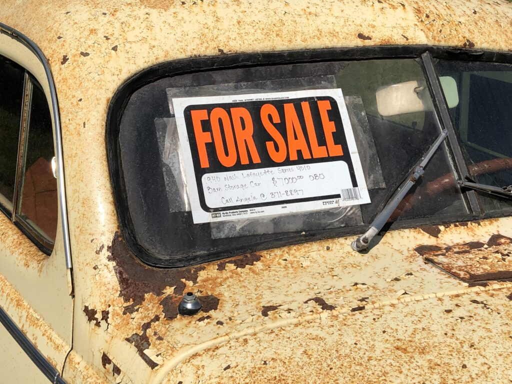 For sale sign on an old car.