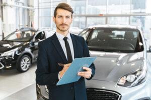 Man in blue business attire holding blue folder