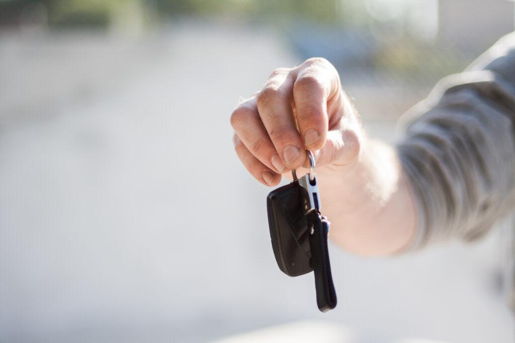Person in grey shirt handing keys