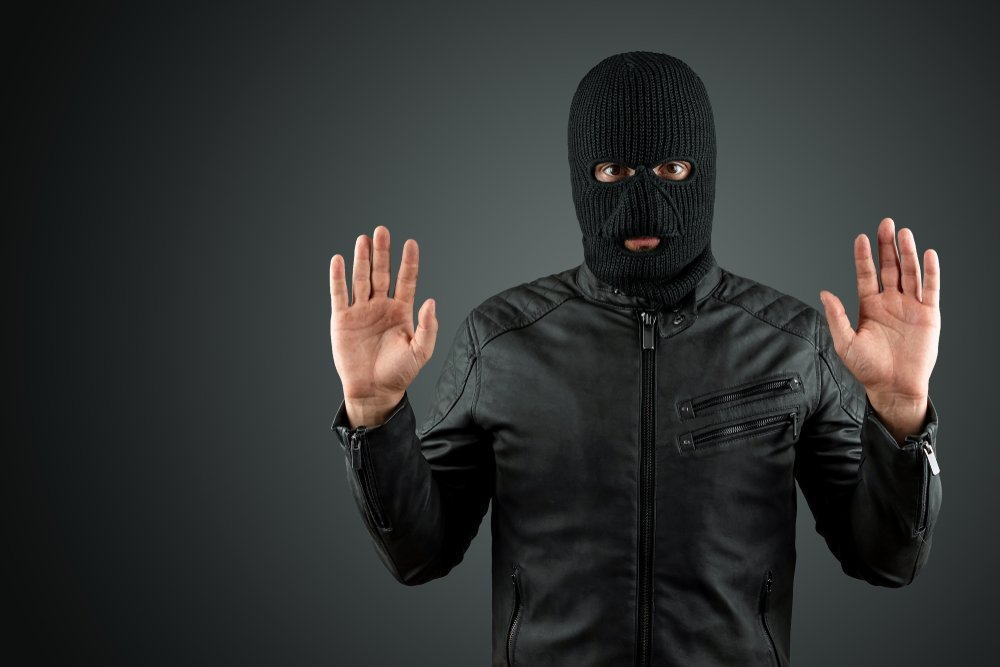 Robber, a thug in a balaclava raised his hands on a black background, surrenders. Robbery, hacker, crime, theft, arrest. Copy space